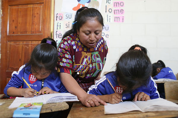 Teacher and students at Fe y Alegría School in Momostenango, Guatemala
